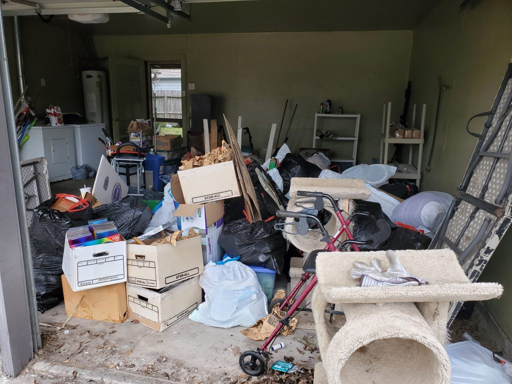 Small garage that is full of junk and debris.